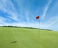 Rote Fahne und das Golf-Feld Lizenzfreie Stockbilder