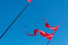 Rote Fahnen flattern im Wind gegen den blauen Himmel Stockfotografie