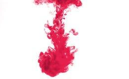 Rote Farbe, die im Wasser sich auflöst stockbilder