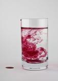 Rote Farbe wird in einem Glas aufgelöst Lizenzfreies Stockbild