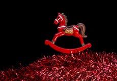 Rote Farbeschaukelpferd über Rotweingirlande, schwarzer Hintergrund Lizenzfreies Stockbild