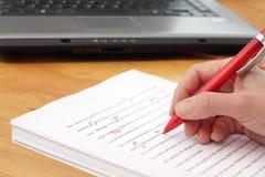 Rote Feder, die eines Manuskriptes durch Laptop liest Stockbild