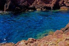 Rote Felsen durch das Meer Stockbilder