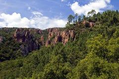 Rote Felsen-Klippen, die über die Überdachung des Blavet Gor steigen Stockbilder