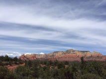 Rote Felsen unter Wolken Stockbild