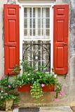 Rote Fenster-Fensterläden mit Blumen-Kasten und Pflanzer Stockfotos