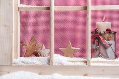Rote Fensterbrett Weihnachtsinnendekoration: Kerze und hölzernes s Stockbilder