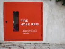 Rote Feuerlöschschlauchspule auf Betonmauer Stockfotos
