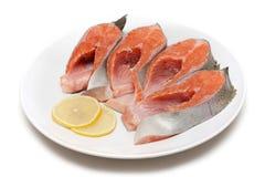 Rote Fische gebissen mit Zitrone auf Platte Stockfotos