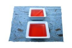 Rote Flüssigkeit auf blauem Papier. Lizenzfreie Stockfotografie