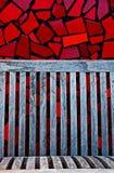 Rote Fliesen und hölzerne Bank Stockbilder