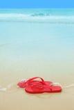Rote Flipflops auf dem Strand Stockfoto