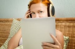 Rote Frau im Bett hörend Musik Stockfotos