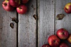 Rote frische Äpfel auf einem hölzernen Hintergrund zerstreut lizenzfreie stockfotografie