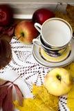 Rote frische Äpfel mit Blättern und Schalen für Tee Lizenzfreie Stockbilder