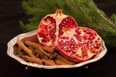Rote Frucht auf einem schwarzen Hintergrund und einer Niederlassung des Weihnachtsbaums Lizenzfreie Stockfotografie