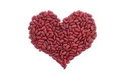 Rote Gartenbohnen in einer Herzform Stockbilder