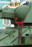Rote Gartennelken auf dem T-34 Stockbilder
