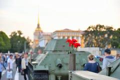 Rote Gartennelken in einer Gewehrpatrone auf einem mittleren sowjetischen Behälter T-34 O Stockfoto