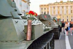 Rote Gartennelken in einer Gewehrpatrone auf einem schweren sowjetischen Behälter KV-1 an Stockbild