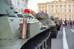 Rote Gartennelken in einer Gewehrpatrone auf einem schweren sowjetischen Behälter KV-1 an Stockfotos