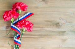 Rote Gartennelken und russisches Flaggenband, die auf dem hölzernen Hintergrund liegt Lizenzfreies Stockfoto