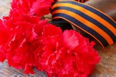 Rote Gartennelken und St- Georgeband auf dem alten Holztisch 9. Mai Tag des Sieges im Großen patriotischen Krieg von 1941-1945 Stockbild