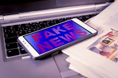 Rote gefälschte Nachrichtenwörter auf Schirm über einer Zeitung Gefälschte Nachrichten, HOKUSPOKUS-Konzept stockbilder