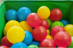 Rote, gelbe, blaue Plastikbälle liegen im grünen Kasten Der Innenraum des Kind-` s Raumes mit vielen bunten Spielwaren Lizenzfreies Stockbild