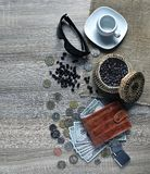 Rote Geldbörse mit amerikanischen Dollar, verschiedenem ausländischem Münzen, Sonnenbrille und Tasse Kaffee auf dem Tisch lizenzfreie stockfotos