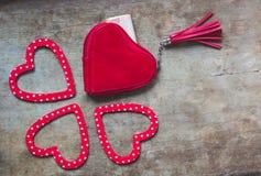 Rote Geldbörse und rotes und weißes punktiertes Herz formten Dekorationen auf hölzernem Hintergrund stockfotos