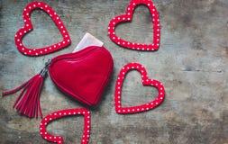 Rote Geldbörse und rotes und weißes punktiertes Herz formten Dekorationen auf hölzernem Hintergrund lizenzfreie stockfotografie