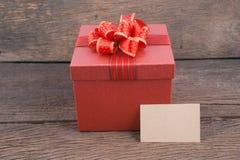 Rote Geschenkbox auf Holz für guten Rutsch ins Neue Jahr Stockbild