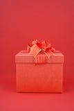 Rote Geschenkbox auf rotem backgroud für guten Rutsch ins Neue Jahr Lizenzfreie Stockfotos