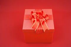 Rote Geschenkbox auf rotem backgroud für guten Rutsch ins Neue Jahr Stockbilder