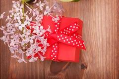 Rote Geschenkbox band rotes Band und Blumen auf hölzernem Hintergrund Stockbilder