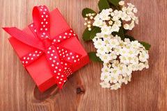 Rote Geschenkbox band rotes Band und Blumen auf hölzernem Hintergrund Lizenzfreies Stockfoto