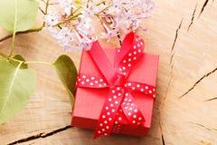 Rote Geschenkbox band rotes Band und Blumen auf hölzernem Hintergrund Lizenzfreie Stockfotos