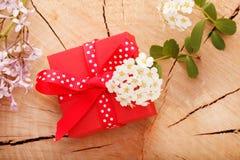Rote Geschenkbox band rotes Band und Blumen auf hölzernem Hintergrund Stockfotografie