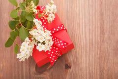 Rote Geschenkbox band rotes Band und Blumen auf hölzernem Hintergrund Lizenzfreies Stockbild