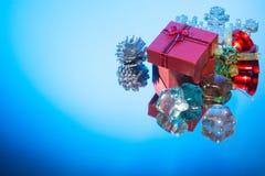 Rote Geschenkbox blaue Weihnachtsverzierung auf einem Spiegel Lizenzfreie Stockbilder
