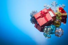 Rote Geschenkbox blaue Weihnachtsverzierung auf einem Spiegel Stockbild