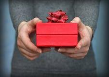 Rote Geschenkbox in den Händen Stockfoto
