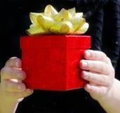 Rote Geschenkbox in den Händen der Frau Stockbilder