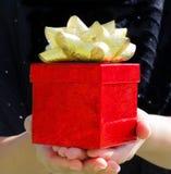 Rote Geschenkbox in den Händen der Frau Lizenzfreies Stockbild