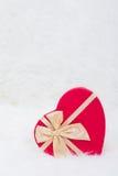 Rote Geschenkbox in der Form des Herzens mit beige Bogen auf weißem Pelz Stockfotografie