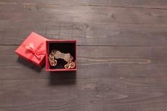 Rote Geschenkbox ist auf dem hölzernen Hintergrund mit leerem Raum Stockfoto