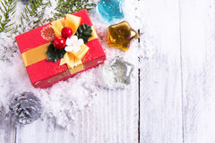 Rote Geschenkbox, Kiefernkegel und grüne Niederlassung auf weißem Holz Stockfotos
