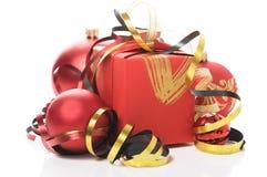 Rote Geschenkbox mit bunten Bändern und Weihnachtsflitter Stockfotografie