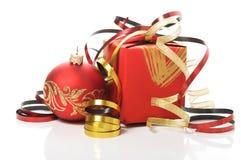 Rote Geschenkbox mit bunten Bändern und Weihnachtsflitter Stockbild